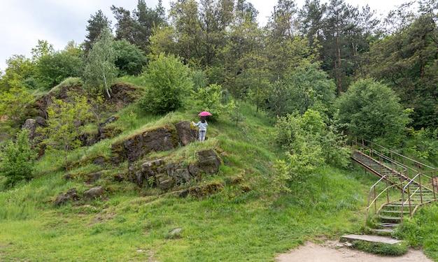 한 여자가 산속의 우산 아래, 녹지로 덮인 바위 사이를 걷는다.