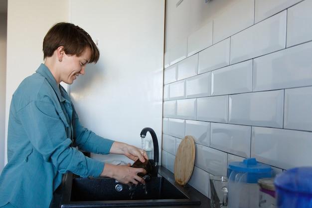 여자가 설거지를한다. 검은 색 싱크대에서 컵 씻기