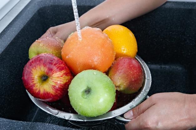 Женщина моет фрукты проточной водой из-под крана на кухне