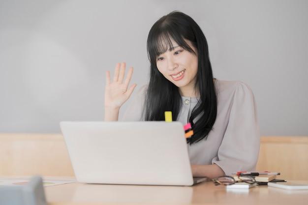 컴퓨터 화면을 맞이하기 위해 그녀의 손을 흔들며 여자