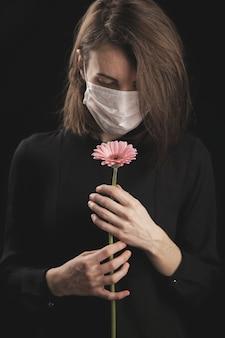 コロナウイルスマスクを着用した女性。美しいピンクのデイジー