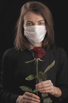 コロナウイルスマスクを着用した女性。美しい赤いバラ