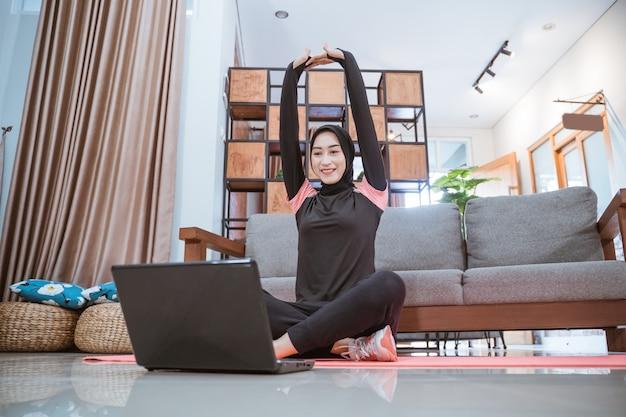 Женщина в спортивной одежде хиджаб сидит, скрестив ноги, потягивая руки вверх, глядя на ноутбук в доме.