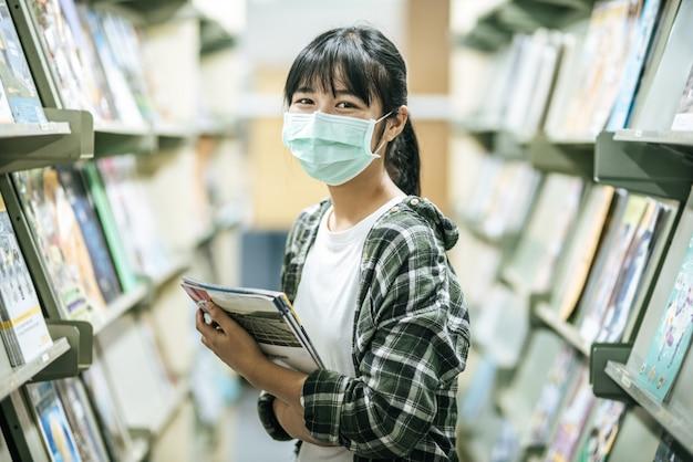 Женщина в маске и ищет книги в библиотеке.