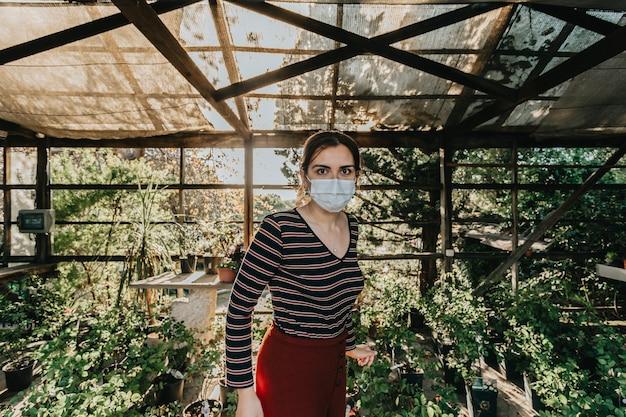 복사 공간이 그녀를 둘러싼 많은 식물과 꽃과 함께 슈퍼 일몰 동안 일부 원예를하는 마스크를 쓰고있는 여자