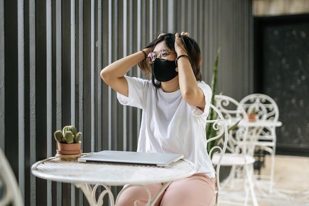 Женщина в маске играет на ноутбуке и обеими руками держит голову