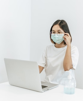Женщина в маске играет на ноутбуке и с бутылкой геля для мытья рук.