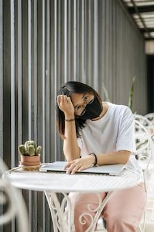 Женщина в маске играет на ноутбуке и положив голову на руку.