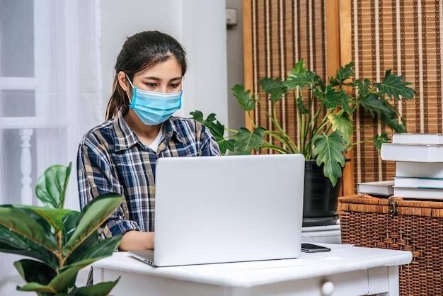 マスクをした女性がノートパソコンを使って仕事をしています。