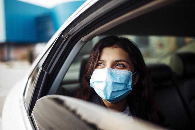 開いている窓の外を横向きに見ている後部座席のタクシー車で医療用滅菌マスクを着用している女性