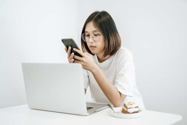 Женщина в белой рубашке, играя на смартфоне и имея ноутбук.