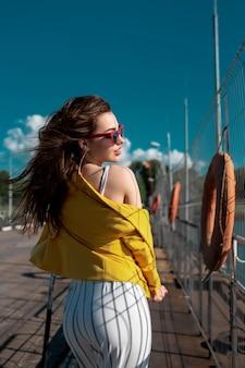 黄色いブラウスとメガネをかけて歩きながら晴天を楽しむ女性