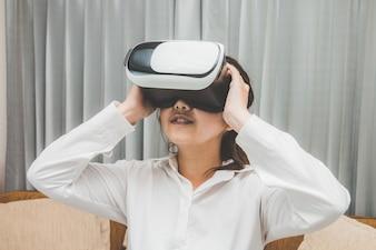 VRガラスで楽しんでいるバーチャルリアリティを身に着けて遊んでいる女性が、ソファーでスマートフォンを使用する