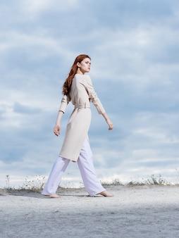 薄着の女性が自然の中の砂と背景の雲の上を歩く