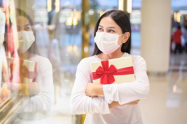 쇼핑몰에서 선물 상자를 들고 보호 마스크를 착용 한 여성, 코로나 19 유행에 따른 쇼핑