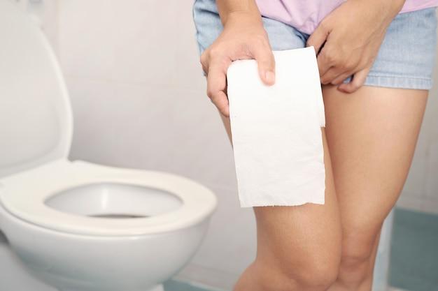 반바지를 입고 화장지를 들고 있는 여성이 화장실에 간다.