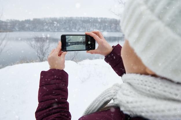 スマートフォンを持って暖かい服を着て、naturviewモードの撮影をしている女性。