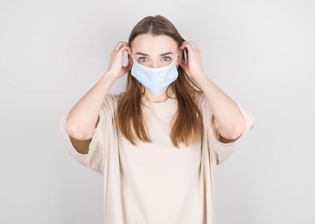 女性は、他の人がコロナウイルスcovid-19およびsars cov2に感染するのを防ぐためにウイルス対策マスクを着用しています