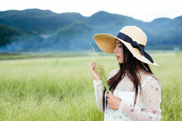 Женщина которая держит траву в ее руках на красивом поле травы с горой.