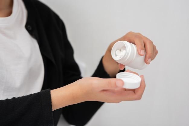 Женщина, которая плохо себя чувствует на кушетке и собирается принимать антибиотики.