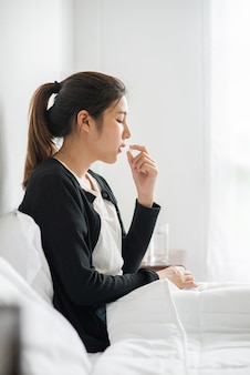 ソファで体調が悪く、抗生物質を服用しようとしている女性。