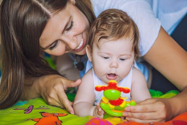 아기를 둔 여성이 눈앞에서 화려한 장난감을 놀아 발달하고 관심을 끌기 위해