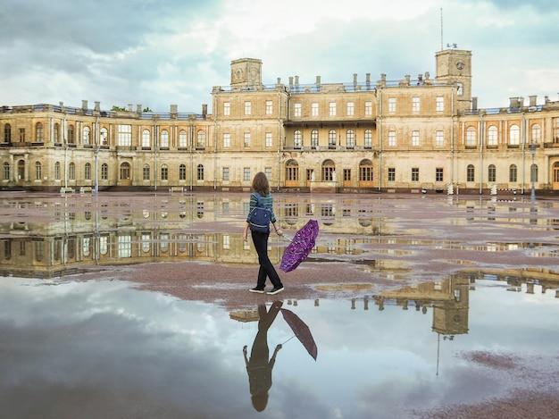 美しい歴史的な場所でバックパックと傘を持つ女性。ガッチナの古代宮殿