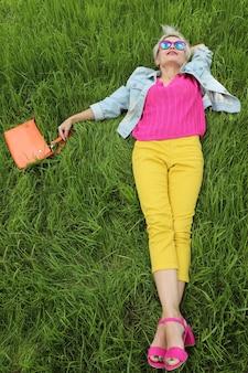 バッグを持った女性は、黄色いズボンとサンダルの青いジャケットの緑の芝生の上にいます