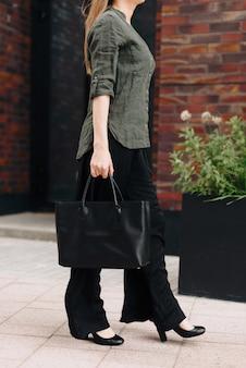 街の背景にバッグを持つ女性