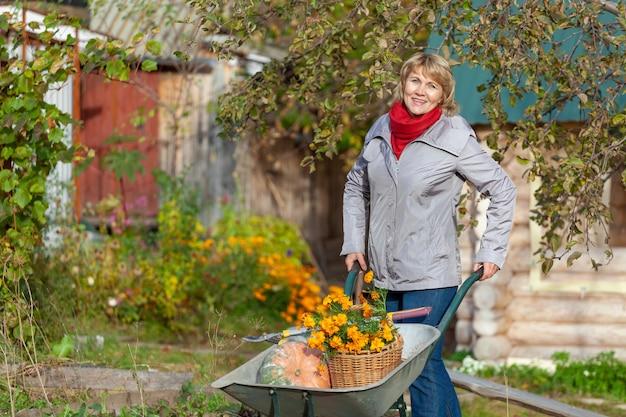 Женщина с корзиной в саду. женщина средних лет в джинсах и куртке держит цветы на фоне осенних деревьев. она держит тачку на заднем дворе.