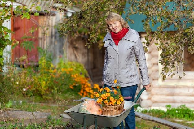 Женщина с корзиной в саду. женщина средних лет в джинсах и куртке держит тачку на заднем дворе.