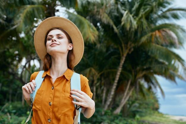 黄色のドレスと帽子の青いバックパックを持つ女性がヤシの木とビーチに沿って歩く