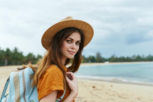 Женщина с синим рюкзаком в желтом платье и шляпе идет по океану по песку с пальмами