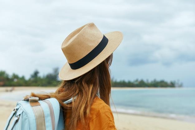黄色のドレスと帽子をかぶった青いバックパックを持つ女性がヤシの木が砂に沿って海沿いを歩く