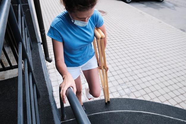 다리가 부러진 여성이 계단을 올라갑니다.