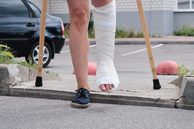 다리가 부러진 여성이 목발로 장애물을 극복합니다.