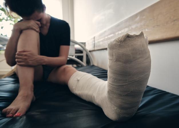足の骨折した女性が病院のソファに座り、骨折後のリハビリテーションを後悔している