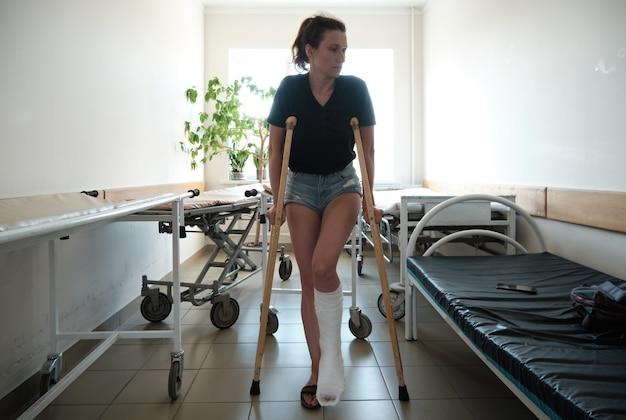 足の骨折した女性が整形外科用松葉杖を使用している足の怪我骨折後のリハビリテーション