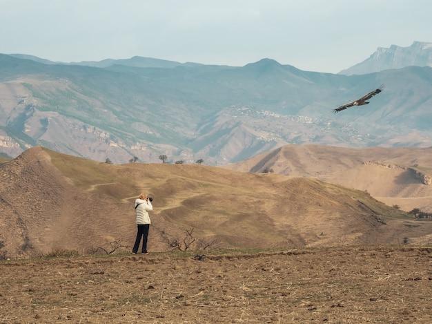カメラを持った女性が山でのワシの飛行を捉えています。