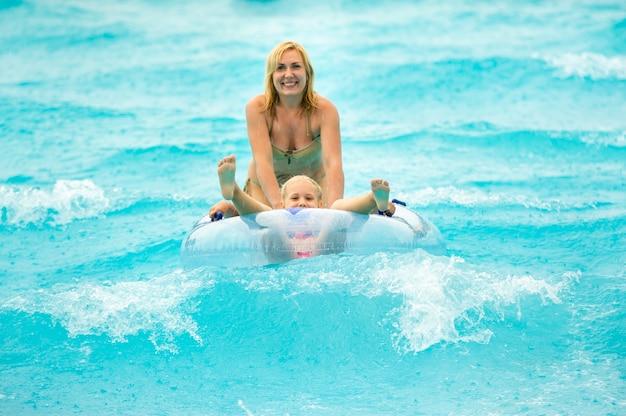 ゴム製の膨脹可能な円の中に子供を持つ女性は雨の中で夏のウォーターパークのプールで遊ぶ