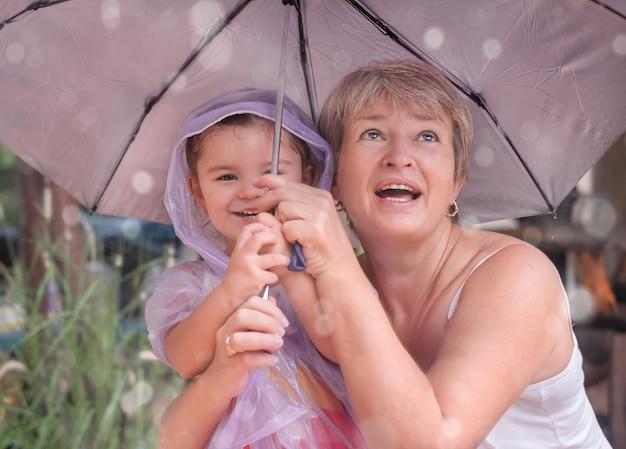 Женщина с ребенком под зонтиком. бабушка и девочка гуляют под дождем
