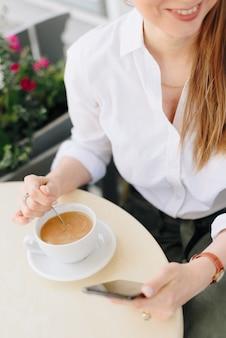 夏の屋外カフェでコーヒーを飲む女性