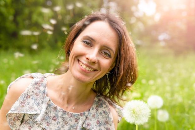 自然の中でタンポポを持つ女性。公園を歩いている幸せな女性。