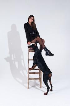 白い背景にドーベルマンの黒いドレスを着た女性。女性が高い階段に座っています