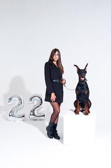 白い背景にドーベルマンの黒いドレスを着た女性。女性がペットを訓練する