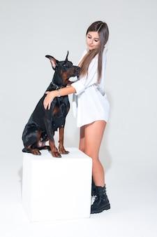 白い背景の上の白いシャツにドーベルマンを持つ女性。魅力的な女性が犬を抱きしめます