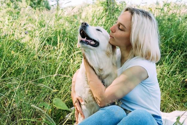 ゴールデンレトリバー犬の女性が芝生で遊んで抱擁します。