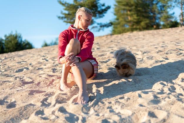 Женщина с собакой на песке, при солнечном свете. для любых целей.