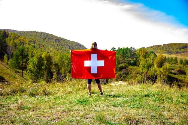 Женщина европейской внешности держит швейцарский флаг на фоне деревьев и гор в солнечную погоду. блондинка со швейцарским флагом в руках
