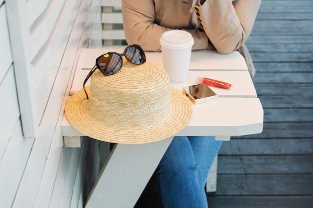 カフェの夏のベランダのテーブルにコーヒーを片手に女性が座っている。